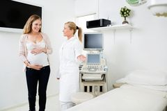 Gynecologist Showing Bed To Pregnant Woman Stock Photography