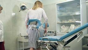 Gynekolog som frågar den kvinnliga patienten att sitta på gynekologisk stol för undersökning lager videofilmer
