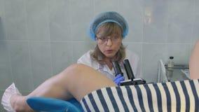 Gynekolog som undersöker kvinnlig tålmodig användande colposcope lager videofilmer