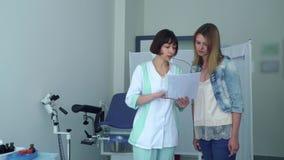 Gynekolog tala med ung tålmodig visning henne resultat av det medicinska provet stock video