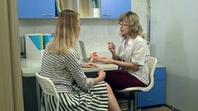 Gynekologdoktor som konsulterar den kvinnliga patienten som använder livmoderanatomimodellen arkivfilmer