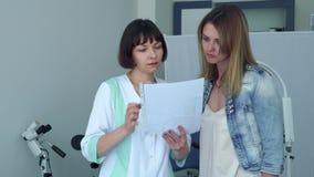 Gynekologen diskuterar resultaten av det medicinska provet med den unga kvinnan lager videofilmer