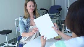 Gynekologen ger resultat av provet till en ung kvinna stock video