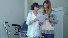 Gynekologen som talar med den unga kvinnan och, visar henne resultat av det medicinska provet lager videofilmer