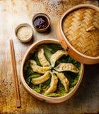Gyoza dumpling in bamboo steamer, sesame and sauce Stock Photo
