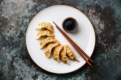 Gyoza dumplings on plate, chopsticks and sauce Royalty Free Stock Images