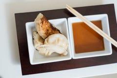 Gyoza-Mehlklöße mit Soße und Essstäbchen Lizenzfreies Stockbild