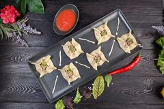 Gyoza with spinach, ricotta and lamb on a black plate on a dark wooden background royalty free stock photos