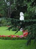 Gypsum bust of a man on a green lawn in a park. Among the beautiful flowers and luxurious green firs. royalty free stock photography