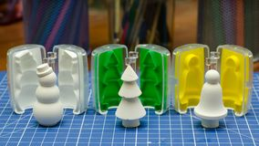 Gypsum snowman, christmas tree and bell with molds. On the blue Stock Photo
