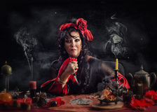 Gypsy bewitch doing unforgivable curse ritual. Portrait of gypsy witch doing deadly curse ritual with a knife and playing cards. Mature sorceress wearing red Stock Photography