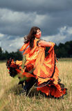 Gypsy dance. Gypsy girl in an orange dress dances in a field Royalty Free Stock Photography