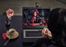 Gypsy enchantress doing insanity curse ritual online. Unfocused back view on women sitting at black desk with laptop. Worried black-haired women looks at gypsy Royalty Free Stock Photo