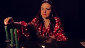 Gypsy fortune teller at the divination table lights candles. The average plan stock video footage