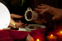 Gypsy fortune teller holds a coffee cup for fortune telling Royalty Free Stock Images