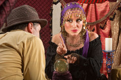 Gypsy Fortune Teller. Pretty gypsy lady pointing with finger over crystal ball stock photos
