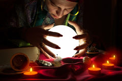 Gypsy fortune teller staring in crystal ball Stock Images