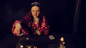 A gypsy fortune teller at the table by candlelight reads the future on the cards in the smoke. The average plan stock video footage