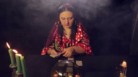 A gypsy fortune teller at the table by candlelight reads the future on the cards in the smoke. The average plan stock video