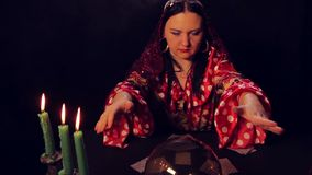 The gypsy fortune teller at the table by candlelight reads the future in a magic crystal. The average plan stock video