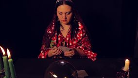 Gypsy fortune teller at the table by candlelight spreads fortunetelling cards. The average plan stock video