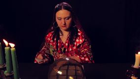 Gypsy fortune teller at the table by candlelight spreads fortunetelling cards. The average plan stock footage