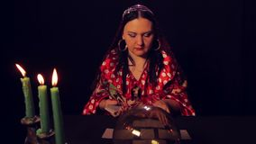 Gypsy fortune teller at the table by candlelight spreads fortunetelling cards. The average plan stock video footage