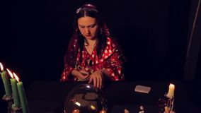 Gypsy fortune-teller at the table by candlelight wonders on the cards. The average plan stock video footage