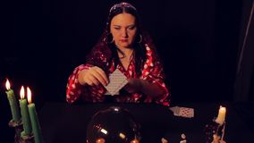 Gypsy fortune-teller at the table by candlelight wonders on the cards. The average plan stock footage
