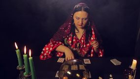 Gypsy fortune-teller at the table by candlelight wonders on the cards. The average plan stock video