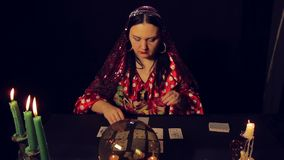 Gypsy fortune teller at the table by candlelight wonders cards. The average plan stock video