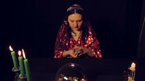 Gypsy fortune teller at the table by candlelight wonders cards. The average plan stock footage