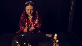 Gypsy fortune-teller at the table by candlelight wonders on white stones. The average plan stock video footage