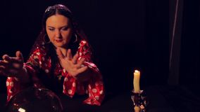 Gypsy fortune teller at the table reading the future in a magic ball. The average plan stock video