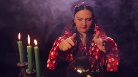 A gypsy fortune teller at the table reads the future in a magic ball. The average plan stock video