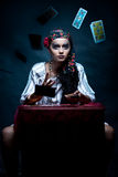 Gypsy fortune teller throwing the tarot cards. A portrait of a gypsy fortune teller, sitting at a table and hrowing the tarot cards that she holds in her hands Stock Photography