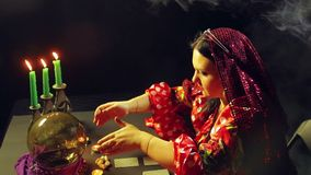 A gypsy in a fortune-telling saloon by candlelight lays out cards for divination on the table. The average plan stock footage