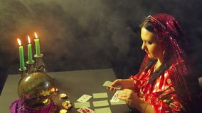 A gypsy in a fortune-telling saloon by candlelight lays out cards for divination on the table. The average plan stock video