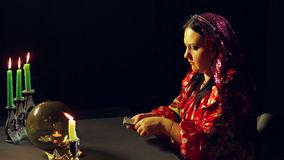 A gypsy in a fortune-telling saloon by candlelight shuffles on the table cards for fortune telling. The average plan stock footage