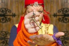 Gypsy girl baroque key. Colorful dressed gypsy girl holds magic prophetess key Stock Photo