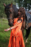 Gypsy girl with a bay horse. Longhaired girl in an orange gypsy dress interacts with a bay horse Stock Images