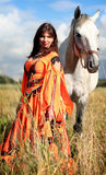 Gypsy girl with a grey horse. Smiling gypsy-dressed girl standing close to a grey horse in a field Stock Photo