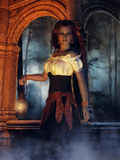 Gypsy girl with a lamp. Fantasy gypsy girl with a lamp in front of a stone well Stock Images