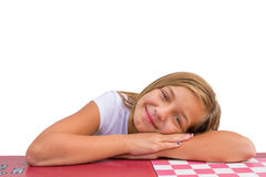 Gypsy girl laying on desk at school smiling Stock Photos