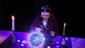 Gypsy kobieta czyta przyszłość nad kamieniami w świetle magicznej balowej błyskawicy zdjęcie wideo