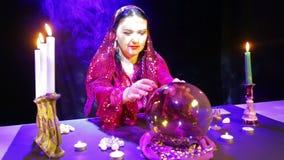 Gypsy kobieta mówi w chuchach dym w czerwonej sukni w pokoju dla pomyślności czyta przyszłość w lustrzanej piłce na zbiory