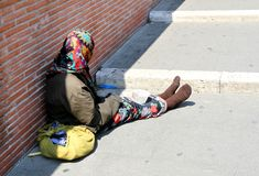 Gypsy with lurid clothes while begging on the street Stock Photography