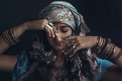 Gypsy style young woman wearing tribal jewellery portrait. On black background Stock Images