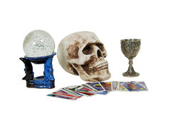 Gypsy tools. Skull with eye sockets and teeth, crystal ball for seeing into the future with miniature bubbles inside, silver antique chalice with grapes and Royalty Free Stock Photos