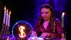 Gypsy w magichsky salonie zastanawia się na białych kamieniach i dolarowy znak pojawiać się w kryształowej kuli zbiory